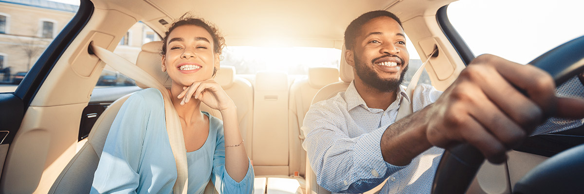 Happy couple driving a new car