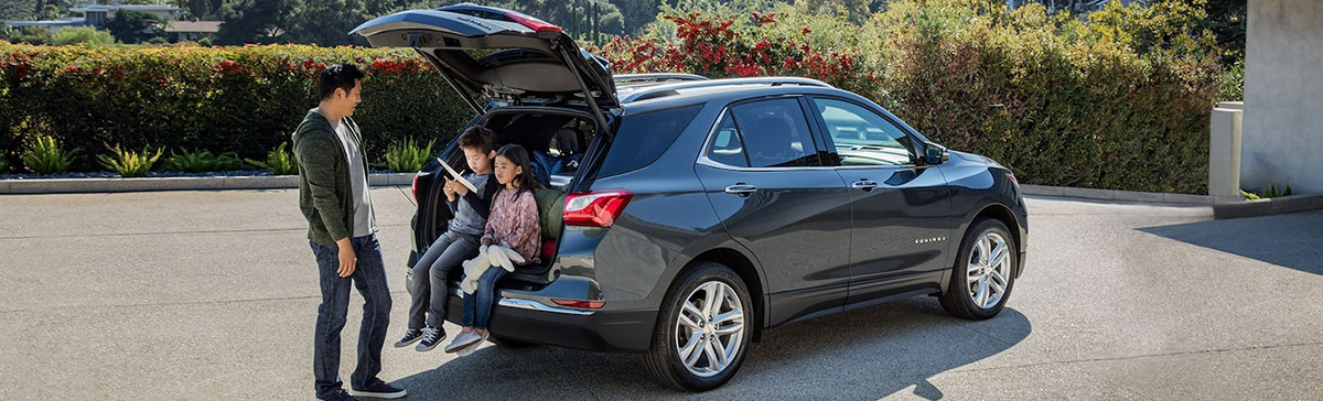 Family hanging out in back of Chevy Equinox