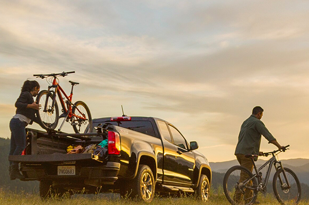 Active couple loading their mountain bikes onto the back of a 2020 Chevrolet Silverado