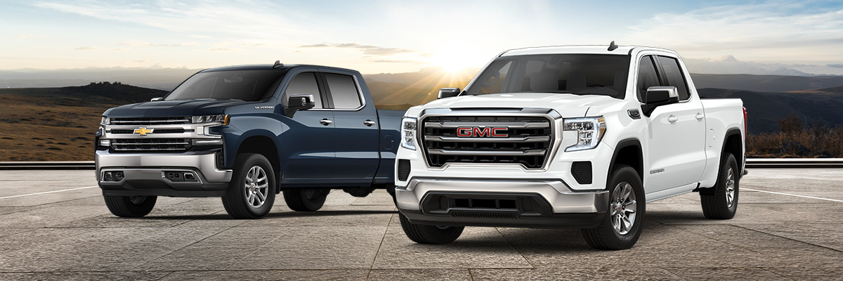 2020 GMC Sierra and 2020 Chevrolet Silverado parked in front of a scenic sunrise